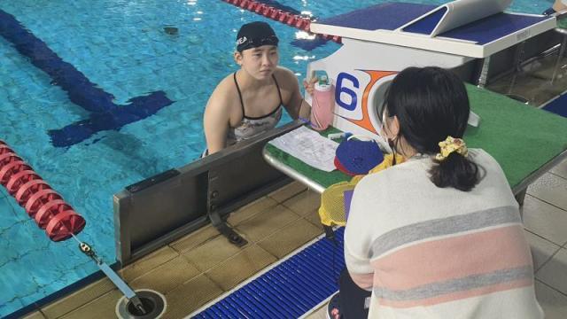 South Korea's Jungeun Kang speaks with her sister Jueun following a training session.