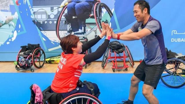 female Para badminton player Yuma Yamazaki sits in a wheelchair and high fives a standing man