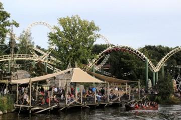 Au premier plan, dans l'eau : un bateau de l'attraction Hollandais Volant. Derrière : un bar-snack. Au fond : la montagne russe Python.