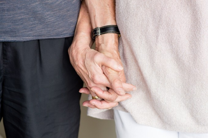Older man and woman holding hands (cropped and close up)