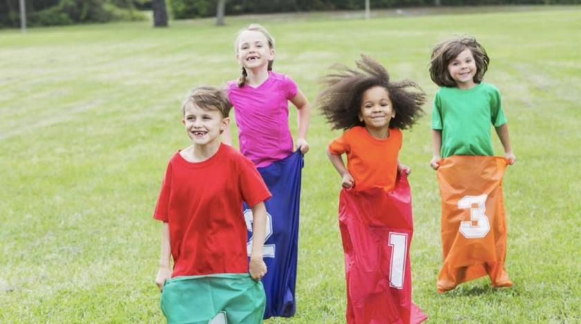 Kids doing a potato sack race