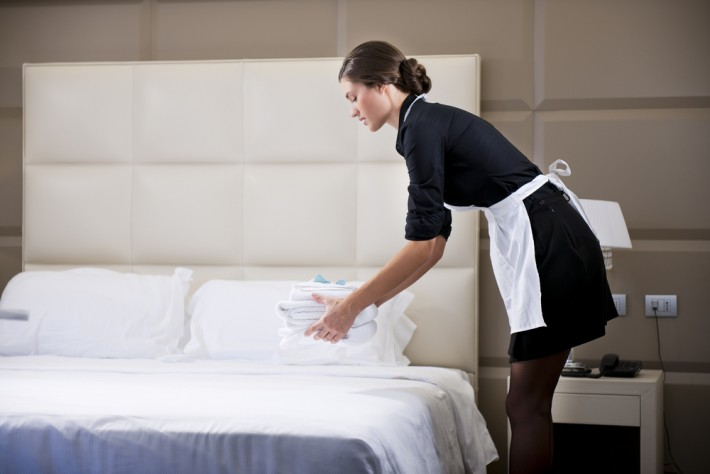 Chambermaid making a bed