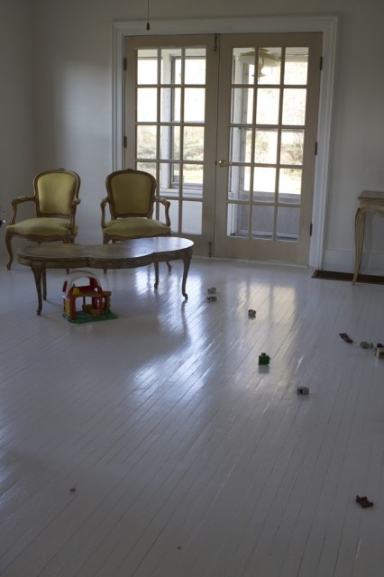 sitting room with toys and green chairs and white floors