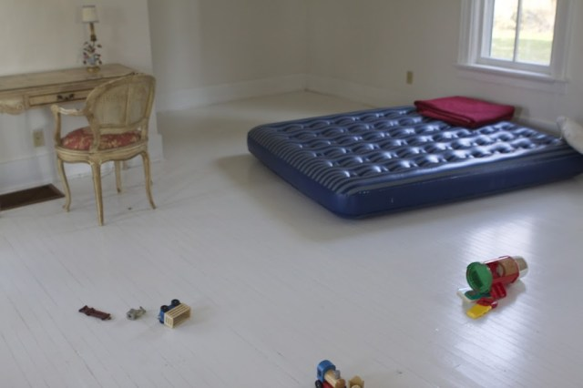 wide shot of white room with desk and toys and air mattress