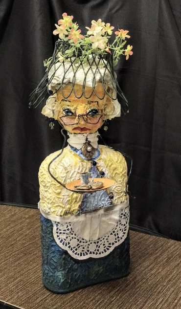 ecccentric woman, wire hat with flowers blue bottle for body, wire frame glasses