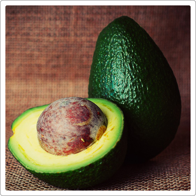 Cut avocado shown in with brown background