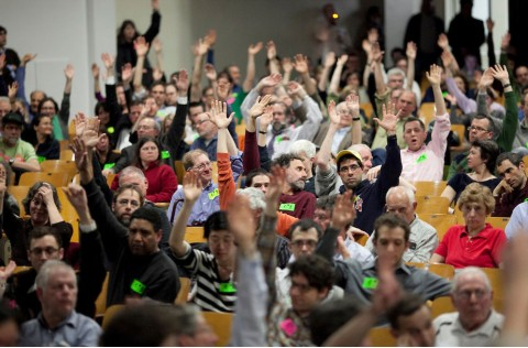 Community members raise hands at participatory budgeting event