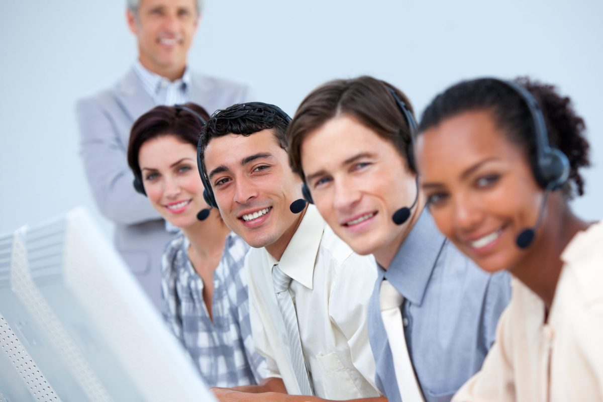 Cheerful business partners working with their manager in a call center