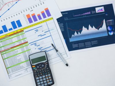 Close-up of graphs, documents and calculator on white background