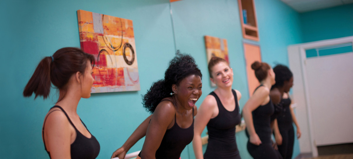 Ladies laughing and screaming at the Barre after workout