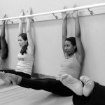 Passion Barre ambassadors doing seated leg lifts under the barre
