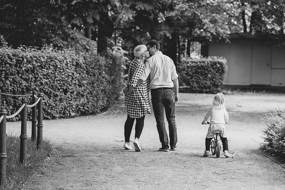 küssende Eltern beim Spaziergang mit Kind - Familienfoto, Familienglück, Familienfotografie, Familienbilder