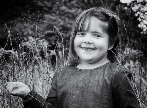 kleines Mädchen in Schwarzweiß in einer hohen Wiese stehend - Familienfotografie, Familienportrait, Familienbilder, Familienfotos, Kinderfotos, Kinderfotografie