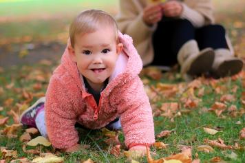 kleines Mädchen krabbelt durch Herbstlaub - Familienfotografie, Familienbilder, Familienfotos, Kinderglück, Kinderfotografie