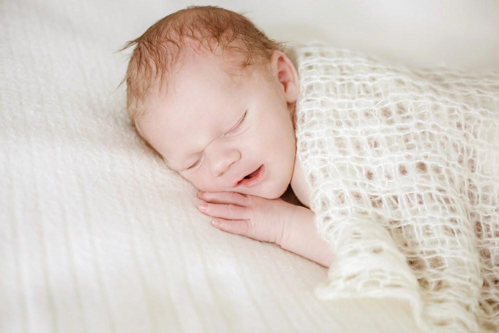 Newborn, Newbornfotografie eines kleinen Jungen in cremefarbenen Tüchern, Neugeborenes