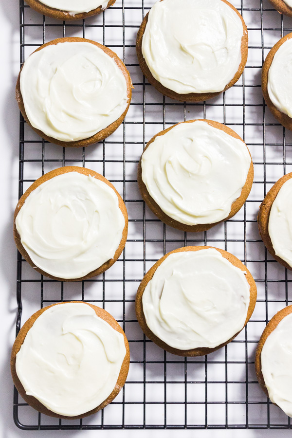 A close up few of gluten free gingerbread cookies topped with cream cheese frosting on a cooling rack.