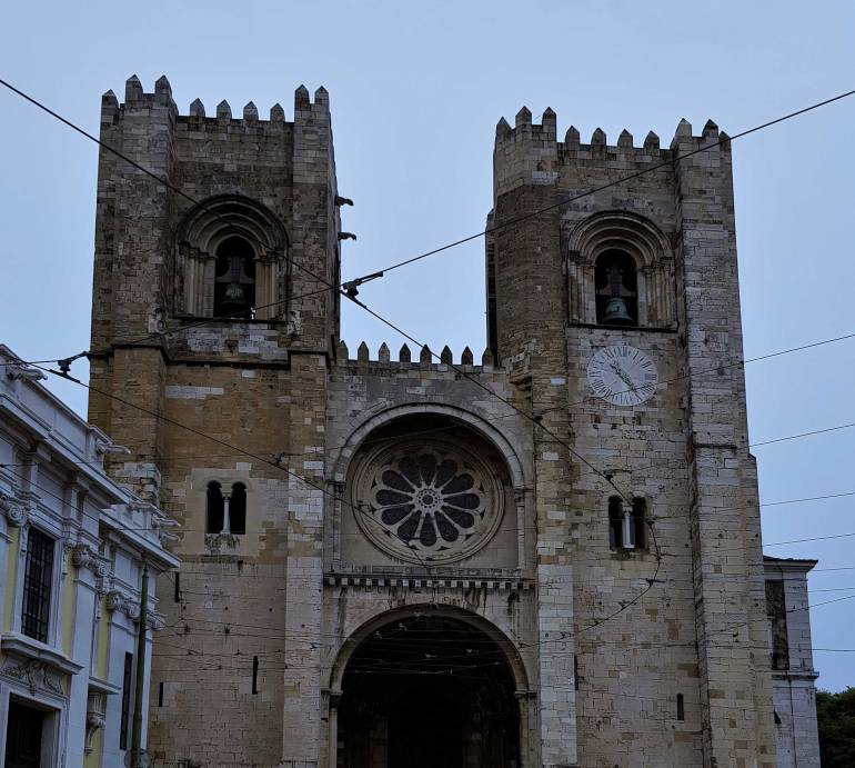 Things to do in Lisbon: Facade of the cathedral in Lisbon.  Electricity cables for the city's trams criss-cross infront.