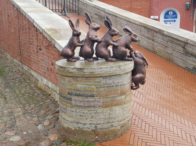 Sculpture of 5 hares with 4 pulling the final one up onto the balustrade of a ramp