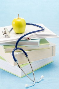 Medical books, apple and stethoscope healthy lifestyle medical research
