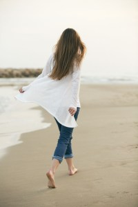 girl walking alone on the beach shore
