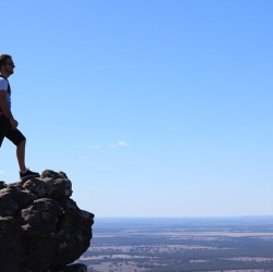 Hombre mirando desde las alturas al horizonte luego de realizar senderismo por la naturaleza.