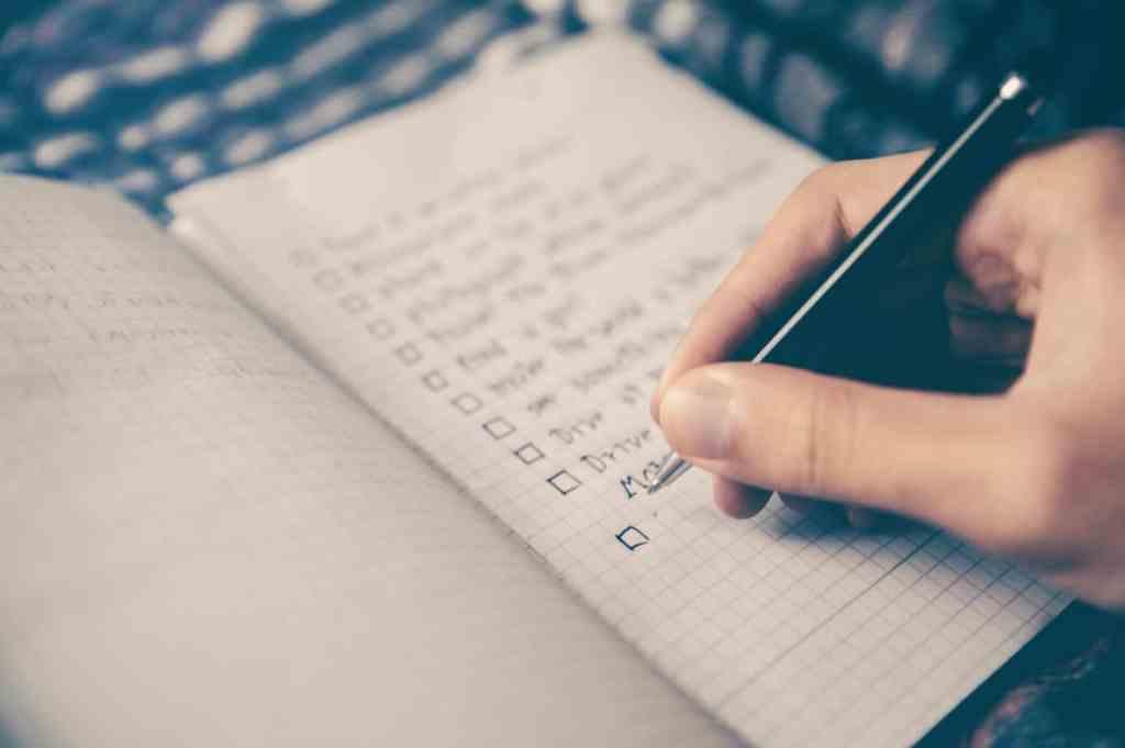 Hand schreibt eine To Do Liste