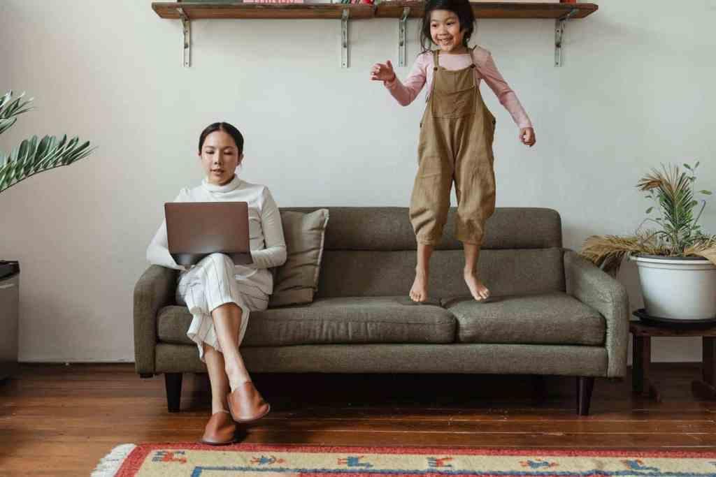 Konflikte lösen -  Kind hüpft auf dem Sofa, Mama arbeitet.