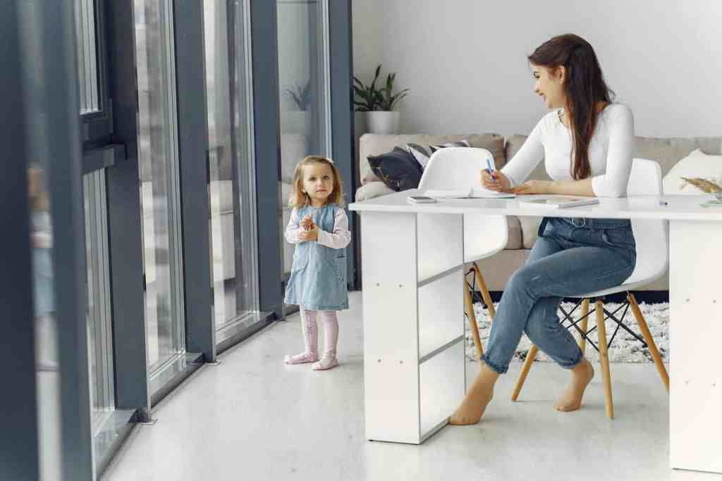Heldenreise als Stiefmutter: Frau sitzt am Schreibtisch und arbeitet, neben ihr steht ein kleines Mädchen.