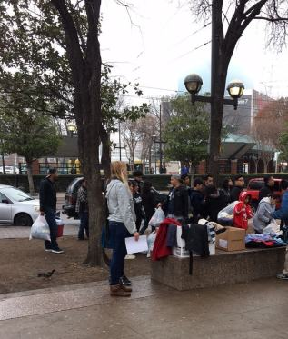 woman hands out clothing for coat drive