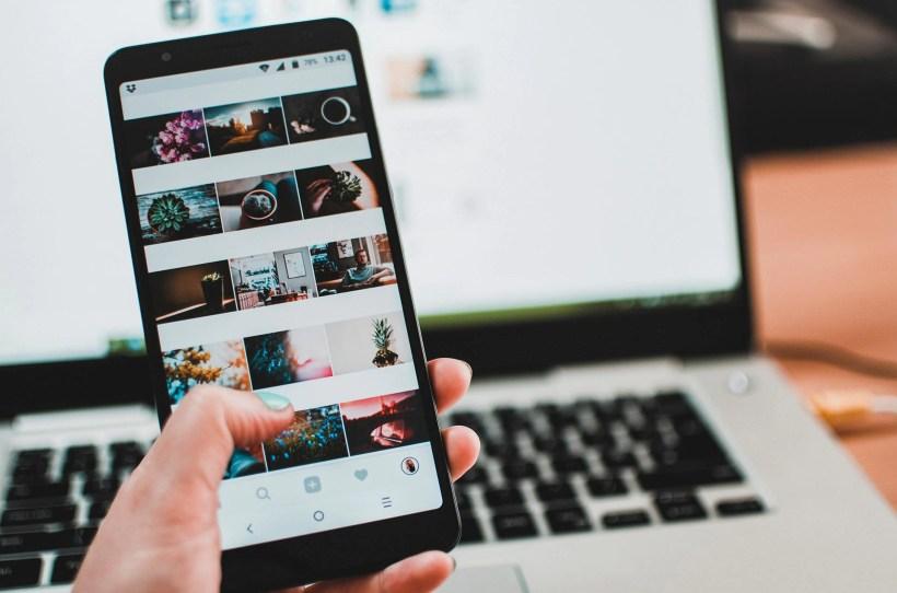 Smartphone mit Instagram Feed vor Laptop