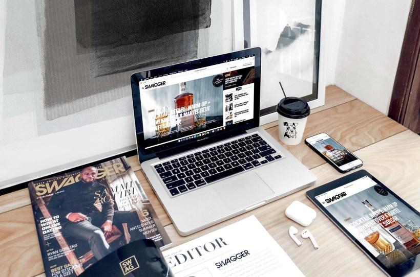 Schreibtisch mit verschiedenen Medien und Laptop