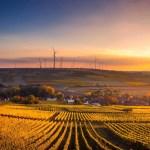 Ländliche Gegend im Sonnenuntergang mit Windrädern am Horizont