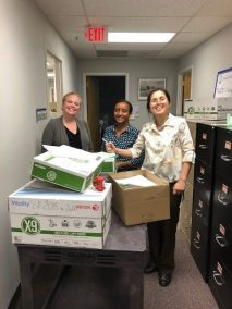 staff smiling and moving boxes