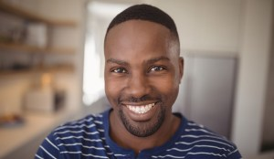 Black man smiling in striped shirt at home