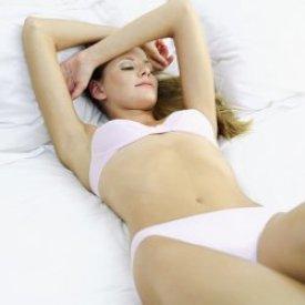 Fiatal nő fehérneműben háton fekszik az ágyon.