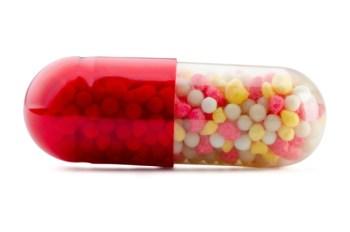 Egy gyógyszer, egy kapszula képe: vörös-átlátszó tokban apró gyöngyök találhatók.