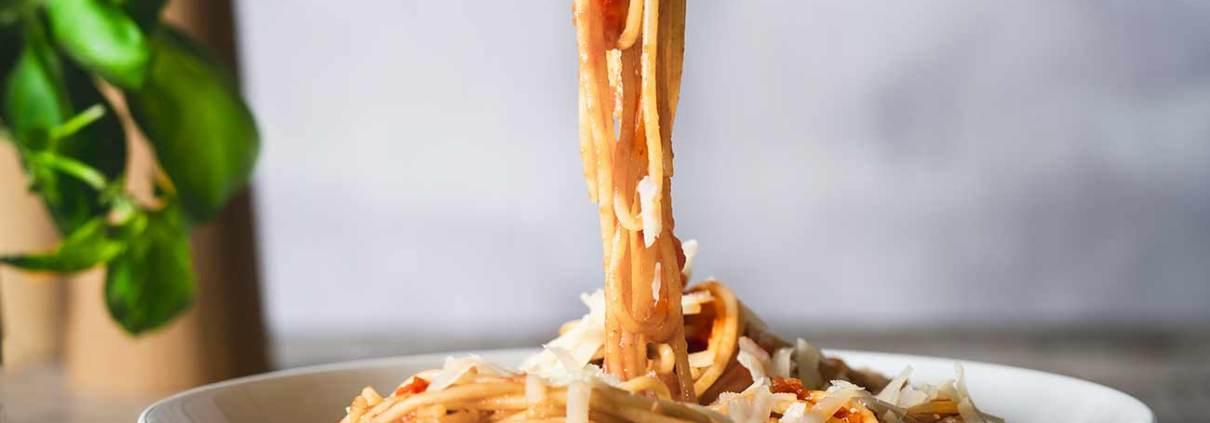 Eine gute Tomatensoße braucht nicht viele Zutaten. Sie muss nur ganz gemütlich ein Stündchen vor sich hin köcheln. In der Zeit kann man die Beine hochlegen, Pasta kochen und Parmesan reiben. Herrlich, so ein Tag!