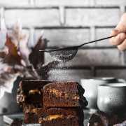 """Brownies with melted caramel core Brownies mit flüssigem Karamellkern Kalorienverweigerer, Karamellhasser und Schokoladenzurückweiser bitte wegschauen, denn hier kommt eine Leckerei auf dem Tisch die es in sich hat. Jeder Bissen dieser Brownies schmilzt köstlich in deinem Mund. Die Ränder sind knackig, die Mitte ist """"chewy"""" und sie haben die perfekte Süße. 1 Springform ca. 20 x 30 cm 250 g Zartbitterschokolade gehackt 250 g Butter 200 g Mehl 1 Pck. Backpulver 100 g Kakaopulver 200 g brauner Zucker 100 g Zucker 1 Prise Salz 2 Päckchen Vanillezucker 8 Eier 200 g Crème fraîche 2 Tafeln Schokolade gefüllt mit Karamell (á 200 g) Puderzucker zum bestäuben Backofen auf 150 Grad Umluft vorheizen Springform mit Backpapier auslegen Schokolade mit der Butter langsam in einem Topf zum schmelzen bringen Mehl, Backpulver, Kakao, braunen Zucker, Zucker, Vanillezucker und Salz vermengen Eier schaumig schlagen, geschmolzene Schokolade unterrühren Mehlmischung zugeben und unterrühren Crème fraîche unterrühren Die Hälfte des Teigs in die Springform geben, Schokolade darauf verteilen, restlichen Teig darüber geben und im Ofen 45 Minuten backen Abkühlen lassen, aus der Form nehmen und auf ein Kuchengitter geben In Stücke schneiden und vor dem Servieren mit Puderzucker bestäuben"""