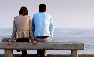 Couple sits on bench at ocean after committing to each other