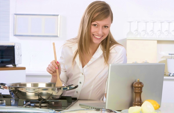 woman-cooking-near-laptop
