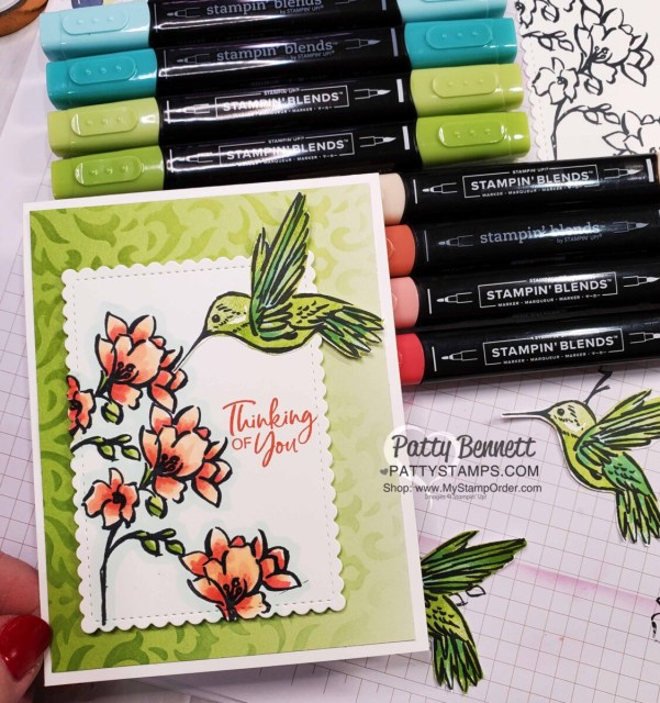 Use Stampin Up! masks, Blending Brushes and ink pads to create a beautiful stenciled background on Oh So Ombre designer paper. Card features the Touch of Ink hummingbird stamp set.  by Patty Bennett