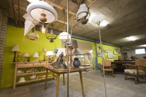 Kringloop Almelo lampen afdeling. Verschillende tweedehands lampen zijn te zien ook de limegroene wand in de winkel is op de achtergrond te zien.