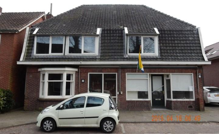 Een kleuren foto van de bestaande jaren dertig renovatie woning Beckumerstraat te Boekelo links het woongedeelte met de erker en rechts de terug liggende ingang in de winkelpui. Architect Enschede Markelo Hengelo Haaksbergen Almelo Oldenzaal Borne