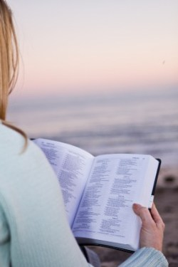 Woman reading her Bible at the beach