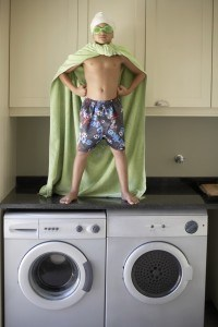 Young Super Hero Standing on Laundry Machines
