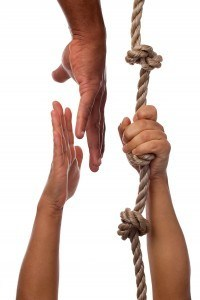 reaching to someone hanging onto a rope