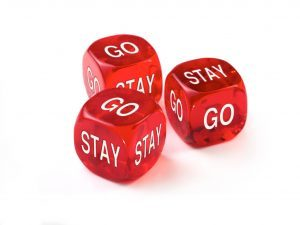 Go or Stay concept with three red dice on a white background.