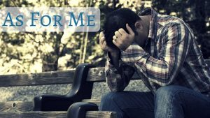 man stopping to pray on a park bench