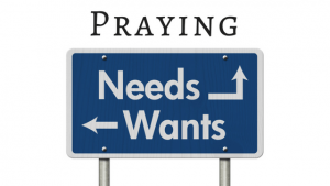 Title Praying and Sign with words wants and needs