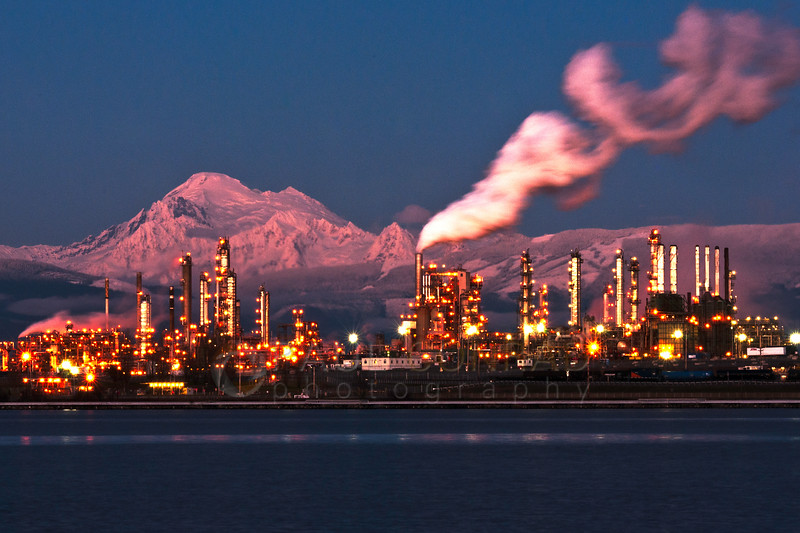 © Paul Conrad/Pablo Conrad Photography - Mount Baker is illuminated by the setting Sun as the lights at the Tesoro refinery in Anacortes, Wash., turn begin to illuminate the petroleum plant.